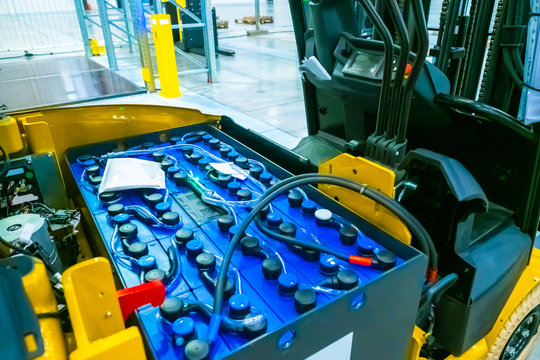Fragment of a forklift. The battery of the truck. Warehouse storage. Automation of the storage process. Yellow forklift in the warehouse. Replacing batteries on a forklift.