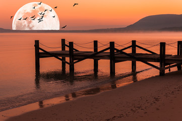 Pier on the beach at sunrise with super moon and flying birds