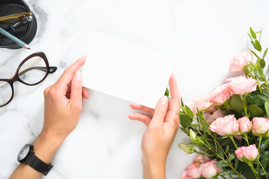 Woman hands holding blank paper card mockup over modern home office desk workspace with stationery, rose flowers bouquet, glasses, Flat lay, top view.