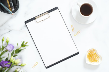 Blank clipboard mockup, golden stationery, flowers bouquet, coffee cup on marble background. Flat lay, top view minimalistic home office desk. Business concept.