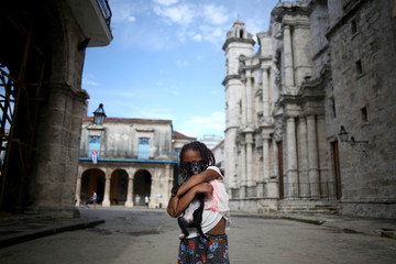 A little girl poses for a picture with her dog outside the Cathedral of Havana, in Havana