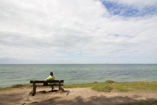 Frau auf Bank am Meer