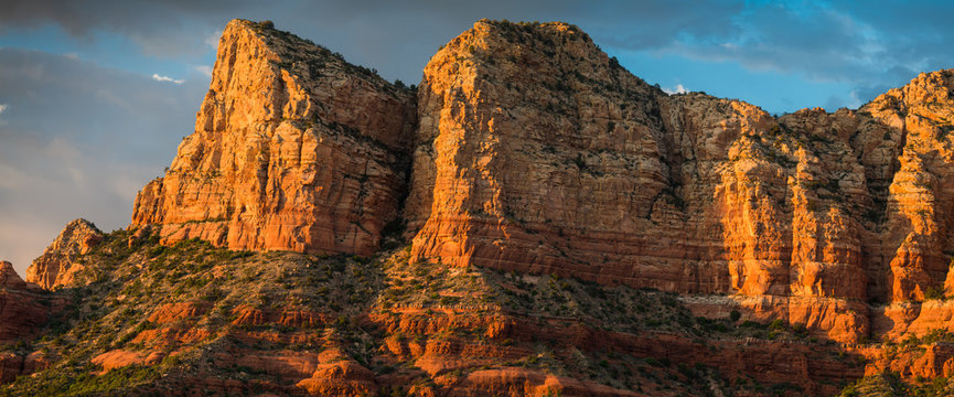 Panorama of beautiful sandstone red rock formations and peaks at golden hour  under a dramatic sky at sunset - Sedona, Arizona