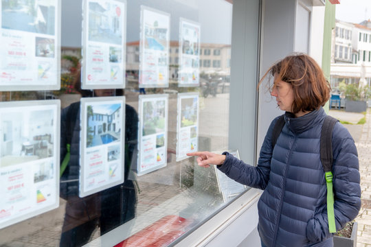 woman in front of shop real estate agency