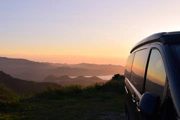 Campervan in the mountains with stunning view to the sea in the sunset