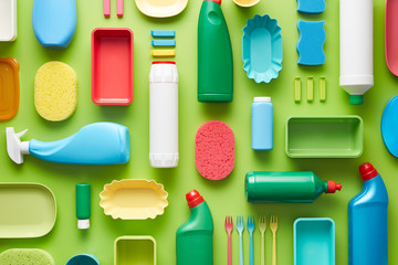 Colorful plastic utensils on green background.