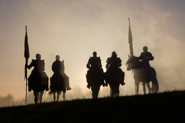 A group of medieval knights silhouetted against the sunset.