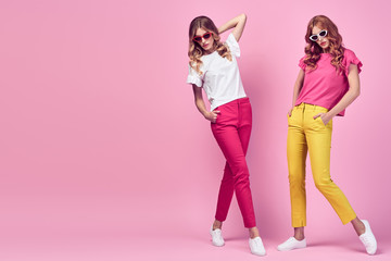 Wall Mural - Fashion. Two Beautiful woman in Trendy summer outfit posing on pink. Graceful sisters friends in yellow coral pants with curly hair, make up. Full length colorful creative fashionable shot