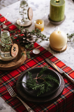 christmas table setting with a pine wreath in the plate
