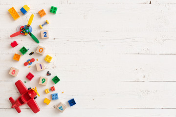 Multicolored plastic and wooden cubes with numbers scattered on a white wooden table. Top view of children's toys and other equipment. Educational games for children. Cubes with numbers 2019.