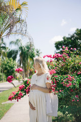 Pregnant beautiful girl near a large tree of flowers