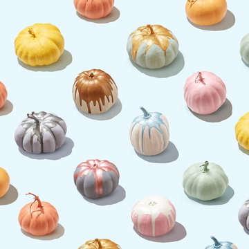 Multicolored painted pumpkins on a light blue background with reflection of the shadows and copy space. layout to halloween. Flat lay