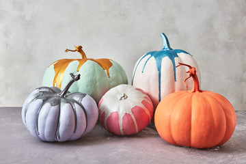 Beautiful bright multi-colored pumpkins with paint splashes on a gray concrete background with space for text. Card