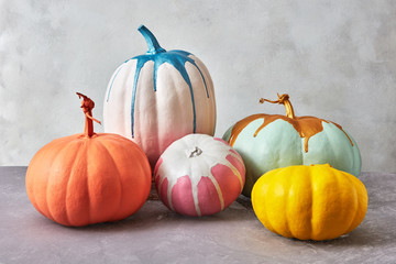 Painted different pumpkins from colorful paint splash on a gray background with space for text. Creative Halloween card