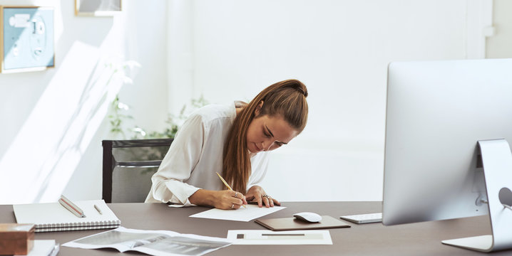 Young female architect sketching a design in an office