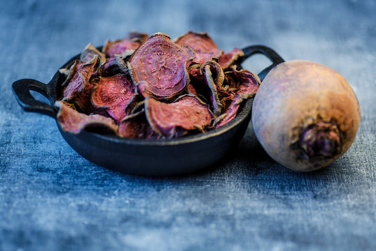 vegetarian pile of healthy beet chips Purple Baked Beet Chips Vegan snacks, vegetable chips in canvas bag and ceramic bowl, rustic still life, selective focus.