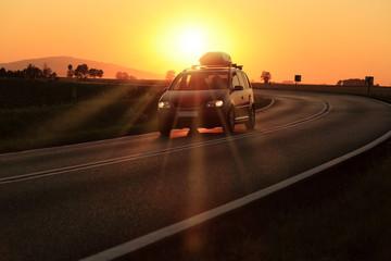 Fototapeta Samochód z bagażnikiem dachowym na zakręcie drogi o zachodzie słońca. obraz