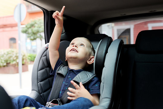 Excited toddler in safety seat in car