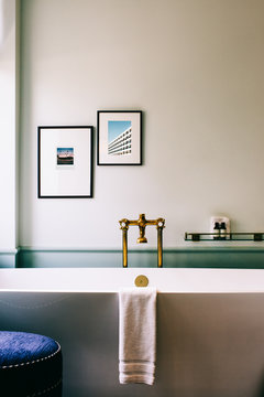 Beautiful Deluxe Bathroom Detail With Framed Photographs Above Bathtub