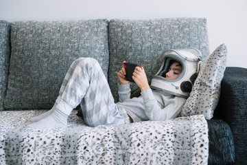 Kid lying on couch and playing with a video game console at home