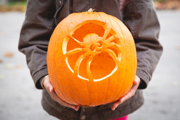 Child holding her finished pumpkin jack o lantern with the image of a spider carved into the surface