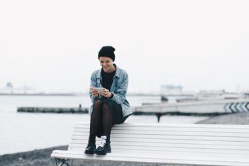 Cheerful woman using smartphone on beach bench