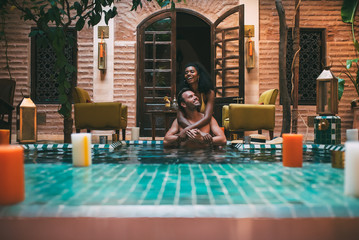 Multiracial couple relaxing in a swimming pool