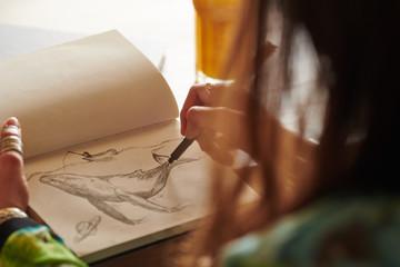 Crop artist drawing whale in sketchbook