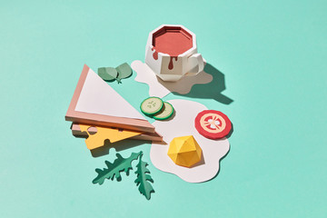 Craft paper sandwich with cheese, fried eggs, sliced tomato, cucumber, arugula and a cup of coffee on a blue background with copy space. Flat lay