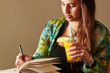Chilling woman with drink drawing in notepad