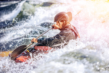 Whitewater kayaking, extreme sport rafting. Guy in kayak sails mountain river