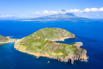 Nature Park of destructed extinct volcano craters of Caldeirinhas, mount Guia near Horta city, Faial island with the peak of Pico volcanic mountain and island in the background, Azores, Portugal