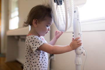 A toddler is learning how a fan works.