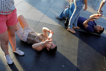 Tourists lie on the floor to take pictures at the Redeeming Christ atop the Corcovado mountain in Rio de Janeiro