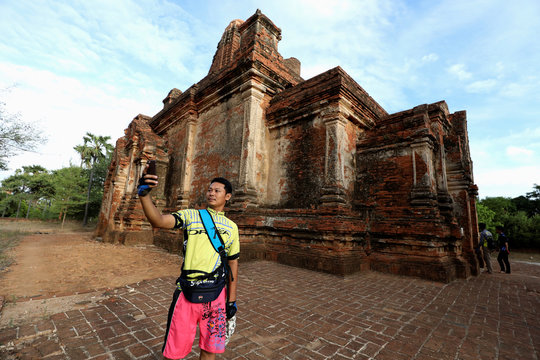 A cyclist takes a selfie with an ancient pagoda to celebrate Bagan being named as a UNESCO World Heritage Site in Bagan