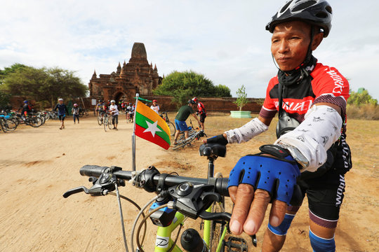 A cyclist with a Myanmar flag attached to his bike tours Bagan to celebrate Bagan being named as a UNESCO World Heritage Site in Bagan