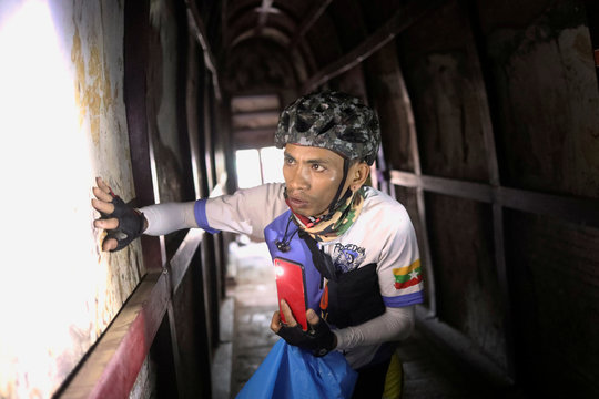 A cyclist uses the light on their mobile phone to view the ancient drawings inside a pagoda in Bagan, Myanmar