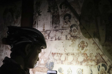 A cyclist uses the light on their mobile phone to view the ancient drawings inside a pagoda in Bagan, Myanmar,