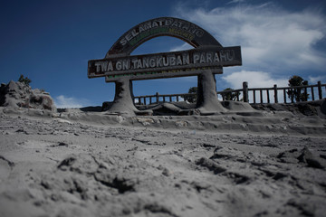 A welcoming sign, covered with volcanic ash is seen after yesterday's volcanic eruption at the tourism area of Mount Tangkuban Parahu in the north of Bandung