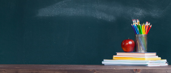 Fototapeta Pencil tray and an apple on notebooks on school teacher's desk. obraz