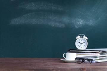 Alarm clock on notebooks on school teacher's desk.