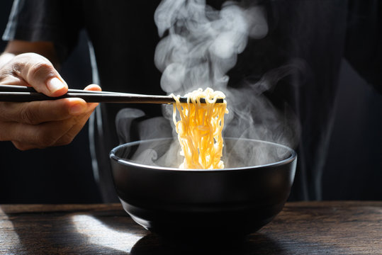 Hand uses chopsticks to pickup tasty noodles with steam and smoke in bowl on wooden background, selective focus. Asian meal on a table, hot food and junk food concept