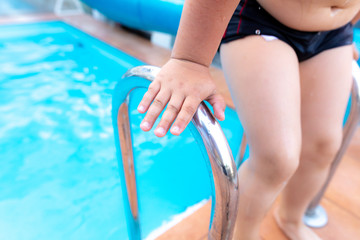 Boy's hand bathing in the pool