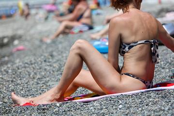 The girl sunbathes on the beach