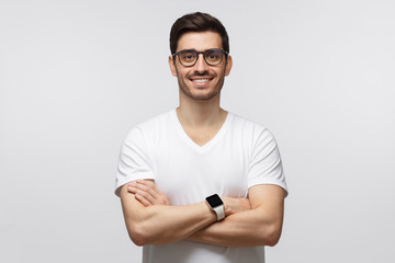 Portrait of smiling man in white t-shirt standing with crossed arms isolated on gray background