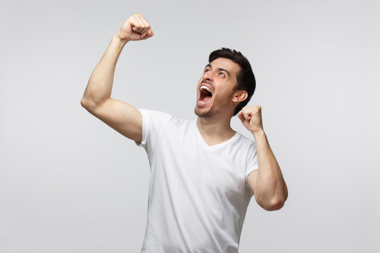 Young successful man screaming yes and raising clenched fist isolated on gray background. People, success, winning and celebration concept
