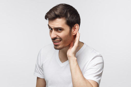 Young man pressing hand to ear trying to hear something better isolated on gray background