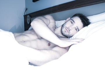 Good looking naked man lying in between white sheets