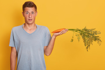 Picture of impressed sweet young man opening his mouth and eyes with shock, holding one carrot on hand, being surprised, fond of vegetables, posing isolated over yellow background in studio.