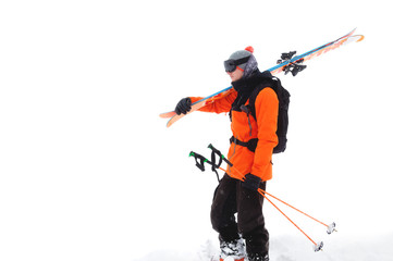 Portrait of a professional athlete skier in an orange jacket wearing a black mask and with skis on his shoulder looks into the camera. Isolated on white